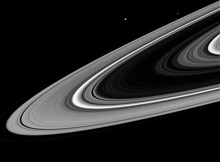 A close up on the rings, with the moons Mimas, Janus and Prometheus visible.